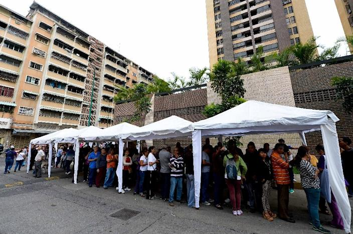 Venezuelans line up to authenticate their signatures for a recall referendum outside the National Electoral Council (CNE) in Caracas, on June 20, 2016 (AFP Photo/Federico Parra)