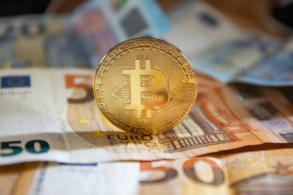 Bitcoin golden physical coin illustration on Euro banknotes of 20 and 50 euros. visual representations of the digital Cryptocurrency Bitcoin with the Euro bill. Bitcoin is a popular digital currency that showed growth and is widely spread, accepted from banks, markets and other services and shops as ways of payments. The exchange rate today for 1 bitcoin blockchain is 9969 euros. Thessaloniki, Greece - August 8, 2020 (Photo by Nicolas Economou/NurPhoto via Getty Images)