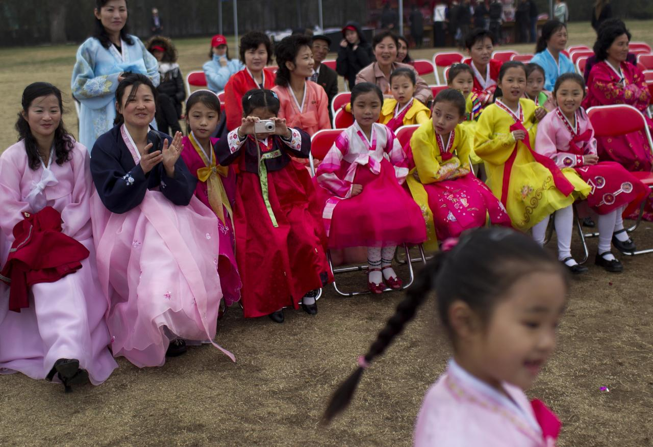 In this April 15, 2011 photo, a girl takes a photo of her friends who were dancing at an event to mark the birthday of Kim Il Sung at a park in Pyongyang, North Korea. (AP Photo/David Guttenfelder)