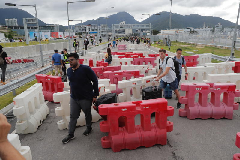 Passengers make their way through barriers put up by protestors near airport in Hong Kong, Sunday, Sept.1, 2019. Train service to Hong Kong's airport was suspended Sunday as pro-democracy demonstrators gathered there, while protesters outside the British Consulate called on London to grant citizenship to people born in the former colony before its return to China. (AP Photo/Kin Cheung)