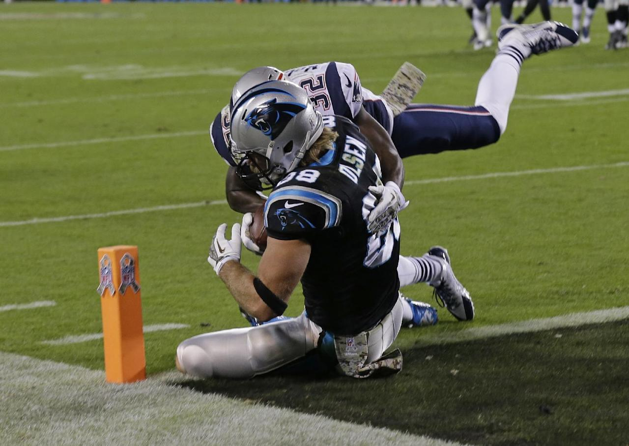 Carolina Panthers' Greg Olsen (88) catches a touchdown pass as New England Patriots' Devin McCourty (32) defends during the second half of an NFL football game in Charlotte, N.C., Monday, Nov. 18, 2013. (AP Photo/Gerry Broome)