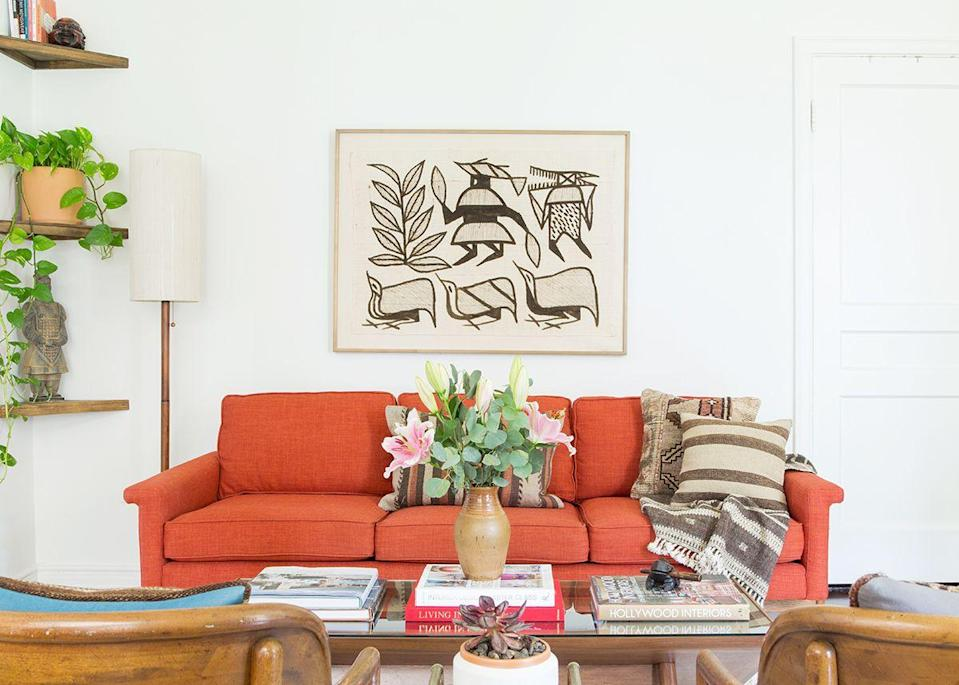 """In the living room, a colorful sofa warms up the entire space. """"The house came with white walls and dark wood floors, so the burnt orange sofa was the first thing I purchased to give the space some color,"""" Cheng tells MyDomaine."""