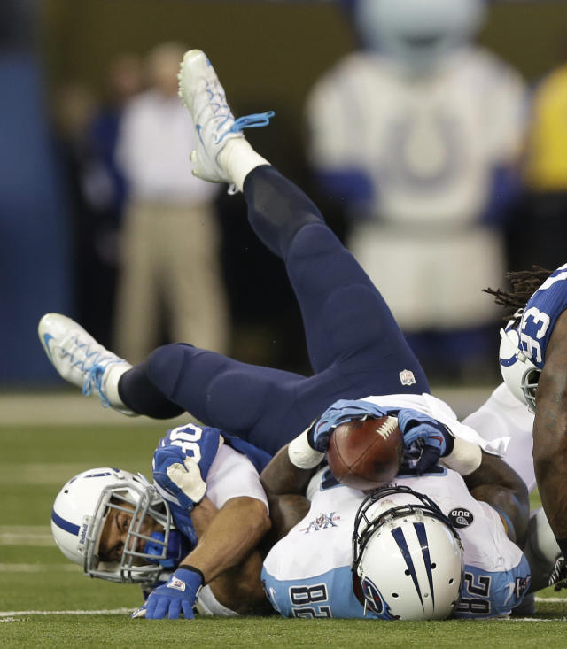 Tennessee Titans' Delanie Walker (82) makes a catch while being tackled by Indianapolis Colts' LaRon Landry (30) during the first half of an NFL football game on Sunday, Dec. 1, 2013, in Indianapolis. (AP Photo/Michael Conroy)