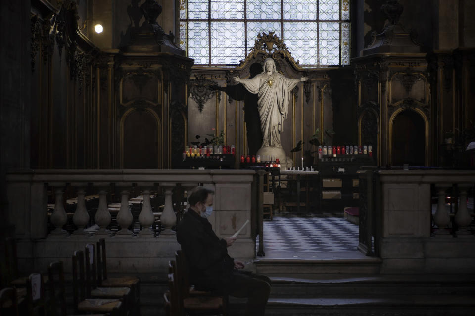 A Catholic worshipper attends the All Saints Day mass in Saint-Sulpice church, in Paris, Sunday, Nov. 1, 2020. France heightened its security alert amid religious and geopolitical tensions around cartoons mocking the Muslim prophet. (AP Photo/Thibault Camus)