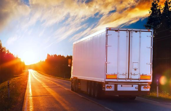 Truck driving into a sunrise