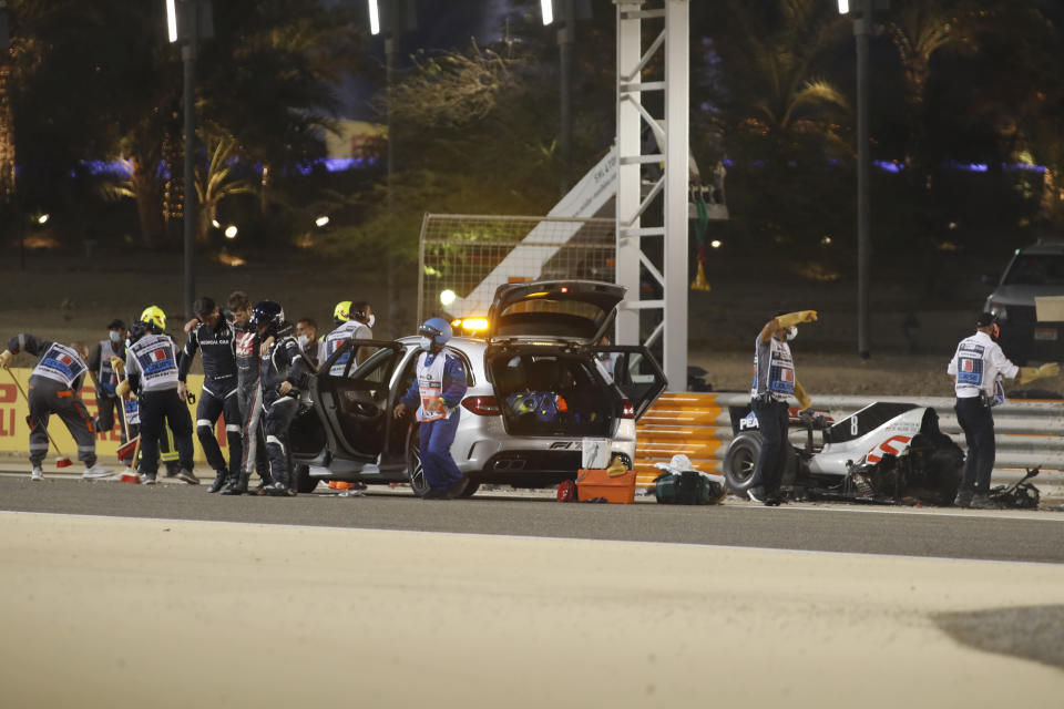 Haas driver Romain Grosjean of France is helped by medical staff after he crashed his car during the Formula One race in Bahrain International Circuit in Sakhir, Bahrain, Sunday, Nov. 29, 2020. (Hamad Mohammed, Pool via AP)