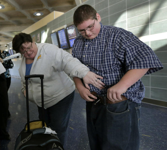 Debbie Alexander checks out her son Jason's baggy-fitting jeans after he returned from a four-month stay at a weight-loss boarding school Friday, Dec. 21, 2012, at the Kansas City International Airport in Kansas City, Mo. Alexander, nearly 100 pounds lighter, was among 14 students from the Independence, Mo., school district to attend the program, losing 756 pounds among themselves. (AP Photo/Charlie Riedel)