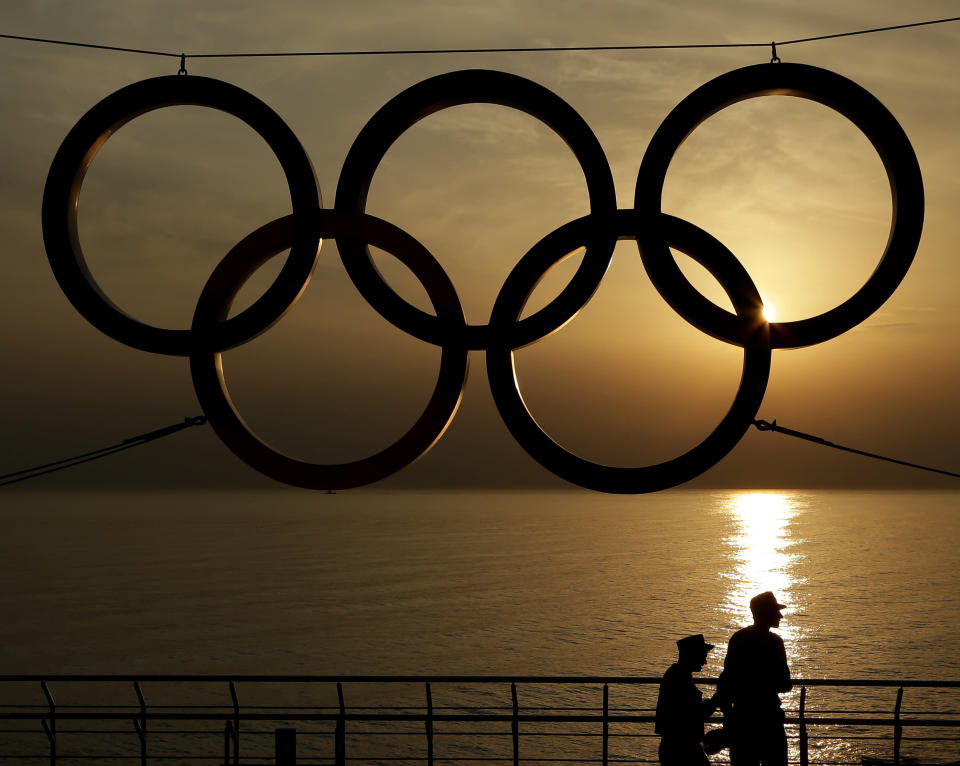 FILE - In this Monday, Feb. 24, 2014 file photo, People stand under a set of Olympic Rings as they watch the sun set over the Black Sea a day after the close of the 2014 Winter Olympics, in Sochi, Russia. U.S. athletes trying to make the Winter Olympics will have to be fully vaccinated for COVID-19 under a groundbreaking new policy announced Wednesday, Sept. 22, 2021 by the U.S. Olympic and Paralympic Committee.(AP Photo/Charlie Riedel, File)