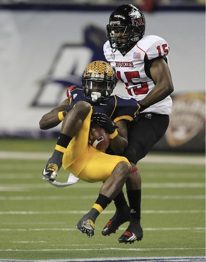 Kent State running back Dri Archer, left, loses control of the ball after a hit from Northern Illinois defensive back Jimmie Ward (15) during the first quarter of the Mid-American Conference championship NCAA college football game on Friday, Nov. 30, 2012. (AP Photo/Carlos Osorio)
