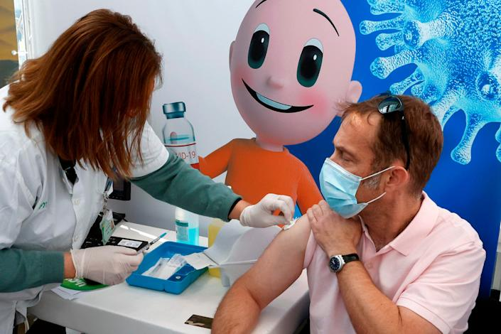An Israeli health care worker vaccinates a man against COVID-19 at Clalit Health Services in Tel Aviv on Jan. 3, 2021.