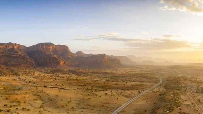 Sunset lit the empty road crossing the dry land of Gheralta Mountains, aerial view, Hawzen, Tigray Region, Ethiopia