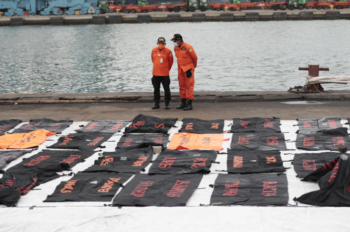 Members of National Search and Rescue Agency (BASARNAS) confer near body bags containing human remains retrieved from from the Java Sea where Sriwijaya Air flight SJ-182 crashed on Saturday, at Tanjung Priok Port in Jakarta, Indonesia, Thursday, Jan. 14, 2021. An aerial search for victims and wreckage of a crashed Indonesian plane expanded Thursday as divers continued combing the debris-littered seabed looking for the cockpit voice recorder from the lost Sriwijaya Air jet. (AP Photo/Dita Alangkara)