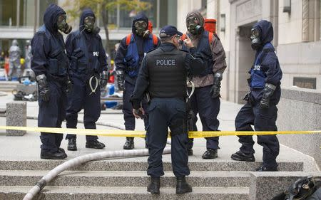 """Police officers wearing gas masks stand in the financial district during a mock """"crisis response"""" exercise in Toronto, October 26, 2014. REUTERS/Mark Blinch"""