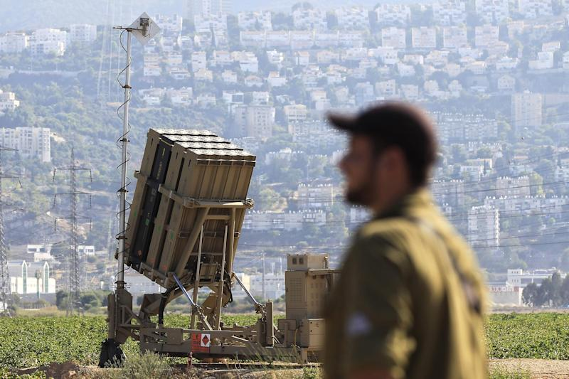 An Israeli soldier is seen next to an Iron Dome rocket interceptor battery deployed near the northern Israeli city of Haifa, Wednesday, Aug. 28, 2013. Israel ordered a special call-up of reserve troops Wednesday as nervous citizens lined up at gas-mask distribution centers, preparing for possible hostilities with Syria. (AP Photo/Tsafrir Abayov)
