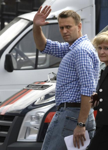 Russian opposition leader Alexei Navalny waves as he heads for questioning at the headquarters of the Russian Investigation committee in Moscow, Russia, Tuesday June 12, 2012. Russia's top investigation agency has summoned several key opposition figures for questioning in an apparent bid to disrupt the first massive protest against President Vladimir Putin since his inauguration for a third term. (AP Photo/Mikhail Metzel)