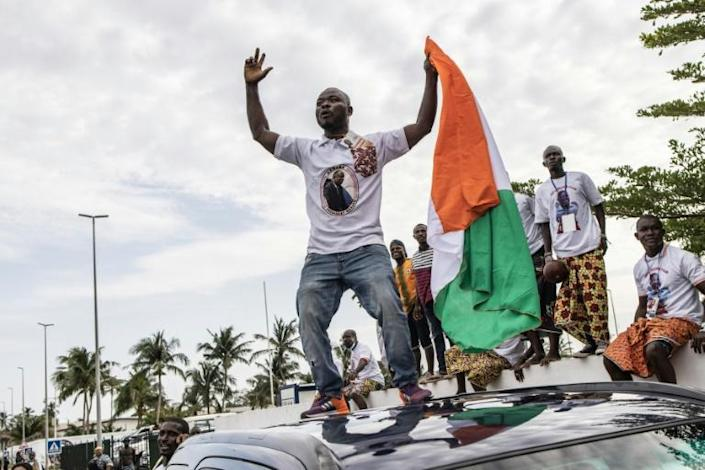 Joy: Gbagbo supporters celebrate as his plane lands