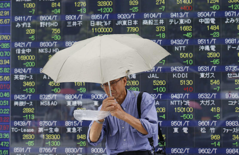 A man walks by an electronic stock board of a securities firm in Tokyo, Monday, July 29, 2013. Asian stock markets fell Monday as traders await a packed schedule of data releases this week in the U.S. and a key meeting of the Federal Reserve. Japan's benchmark Nikkei 225 dropped 2.5 percent to 13,766.09 as the yen continued to reverse from its recent fall. (AP Photo/Koji Sasahara)