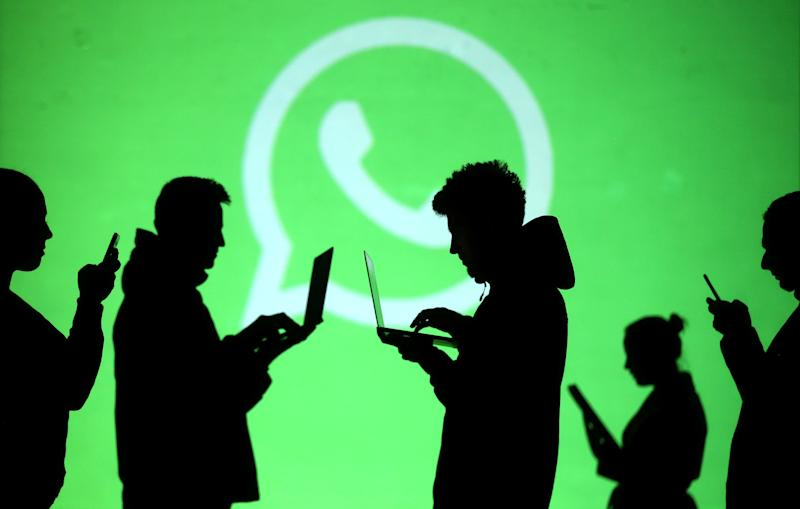 Silhouettes of laptop and mobile device users are seen next to a screen projection of Whatsapp logo in this picture illustration taken March 28, 2018. REUTERS/Dado Ruvic/Illustration