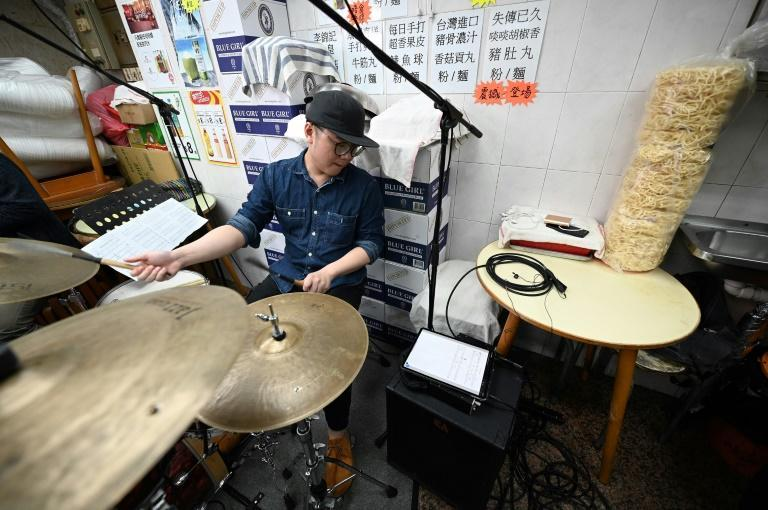 The band does a sound check in the local noodle shop in Hong Kong ahead of a live streaming jazz performance