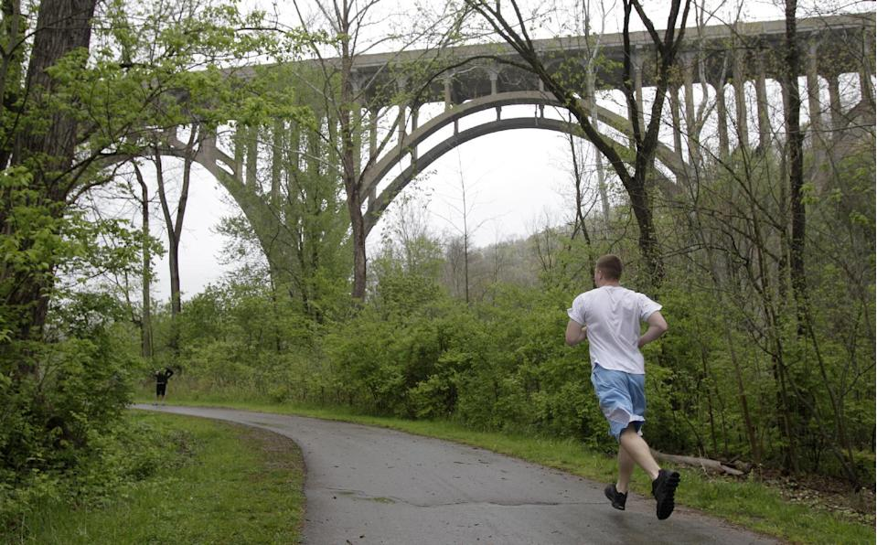 A jogger runs along the tow path approaching a bridge at the Cuyahoga Valley National Park in Brecksville, Ohio, on Tuesday, May 1, 2012. Five men have been arrested for conspiring to blow up the high level bridge over the Cuyahoga River valley, but there was no danger to the public because the explosives were inoperable and were controlled by an undercover FBI employee, the agency said Tuesday in announcing the men's arrests. (AP Photo/Amy Sancetta)