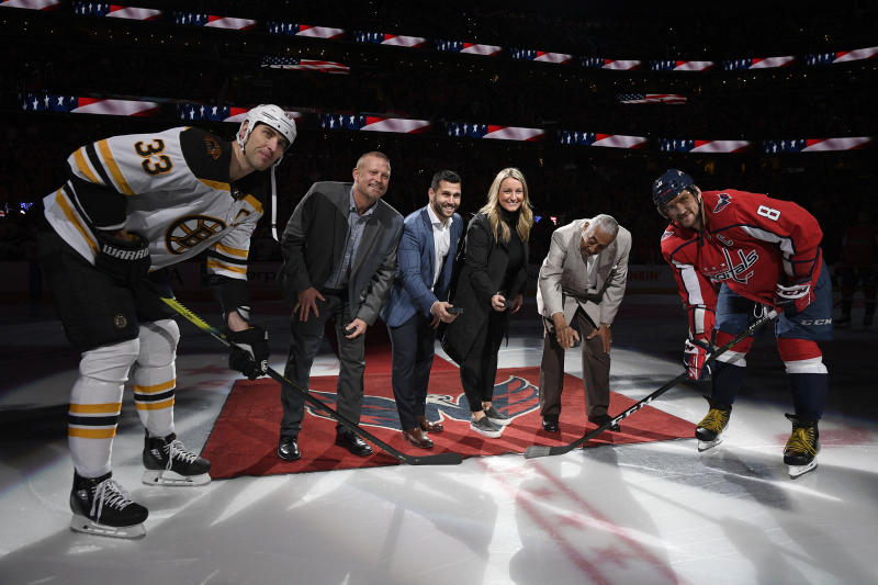 Boston Bruins defenseman Zdeno Chara (33), Washington Capitals left wing Alex Ovechkin (8), of Russia, and the 2019 U.S. Hockey Hall of Fame class, from second left to second right: Tim Thomas, Brian Gionta, Krissy Wendell and Neal Henderson stand on the ice for a ceremonial puck drop before an NHL hockey game, Wednesday, Dec. 11, 2019, in Washington. (AP Photo/Nick Wass)
