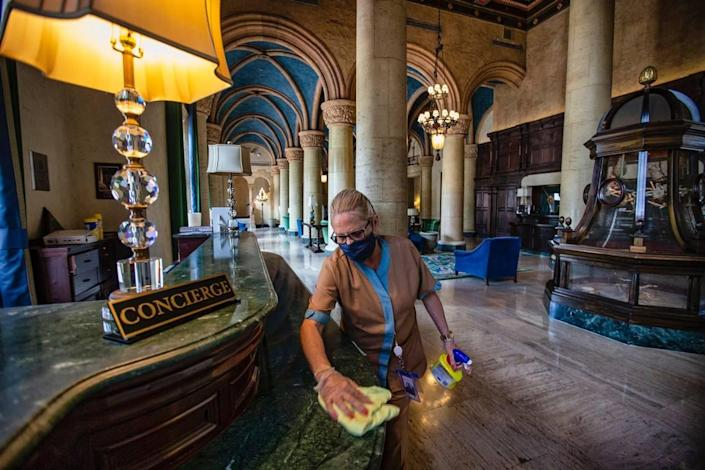 The Biltmore Hotel's guest room attendant Hilda Castillo, 62, disinfects the concierge area of the hotel lobby in advance of its June 1, 2020, opening.