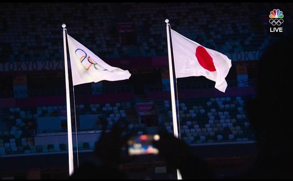 Olympic flag flies next to the Japanese flag as a phone records the moment.