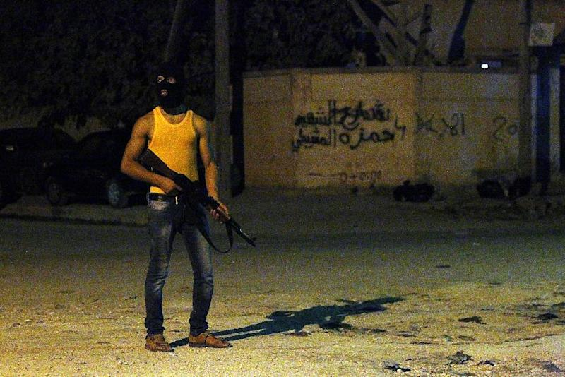 A masked Libyan gunman stands on a street in the eastern city of Benghazi, early on July 29, 2014, a sign of the violence that has engulfed the city (AFP Photo/Abdullah Doma)