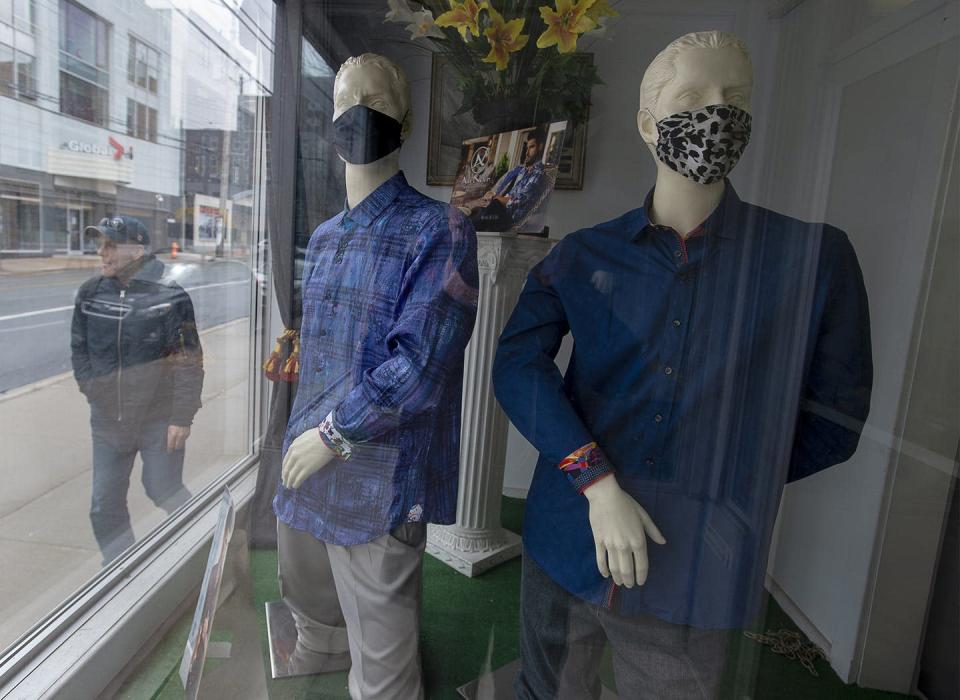 """<span class=""""caption"""">A man heads past a clothing store where mannequins sport face masks in Halifax. Retail workers, long-term care workers and teachers say the media has failed to reflect their pandemic experiences.</span> <span class=""""attribution""""><span class=""""source"""">THE CANADIAN PRESS/Andrew Vaughan </span></span>"""