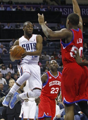 Charlotte Bobcats' Kemba Walker, left, looks to pass as he is guarded by Philadelphia 76ers' Jason Richardson (23) and Lavoy Allen, right, during the first half of an NBA basketball game in Charlotte, N.C., Friday, Nov. 30, 2012. (AP Photo/Chuck Burton)