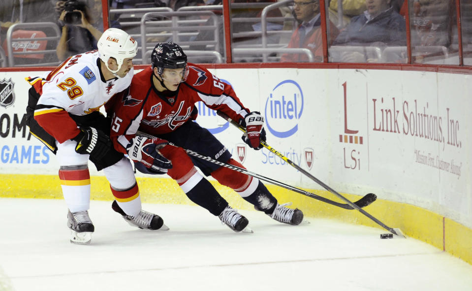 Calgary Flames defenseman Deryk Engelland (29) battles for the puck against Washington Capitals left wing Andre Burakovsky (65), of Austria, during the first period of an NHL hockey game, Tuesday, Nov. 4, 2014, in Washington. (AP Photo/Nick Wass)