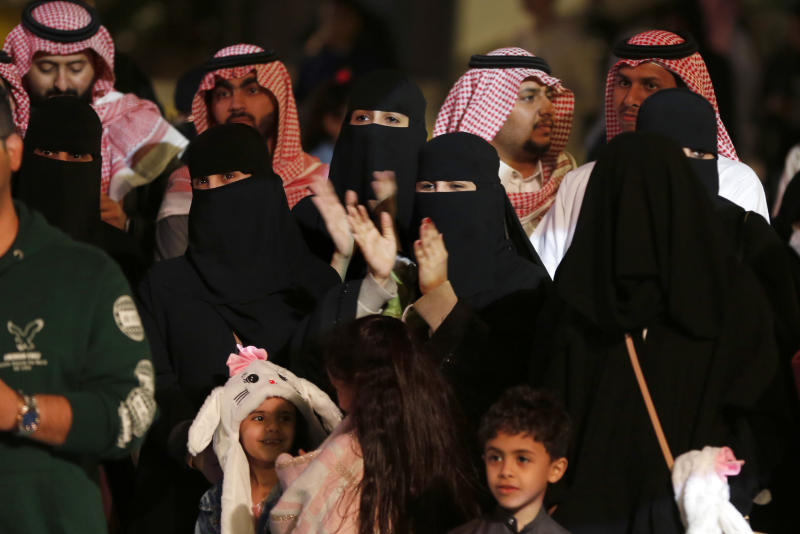 In this Dec. 13, 2019 photo, visitors watch an acrobat player at the Diriyah Oasis amusement park in Diriyah on the outskirts of Riyadh, Saudi Arabia. Hollywood actors, models and social media mavens were invited to Saudi Arabia over the weekend to promote a three-day-long musical festival for young Saudis that took place in the capital, Riyadh. The efforts are aimed at boosting the economy while polishing the country's image abroad and appealing to the young. It's a pivot from just three years ago, when religious police would storm restaurants playing music and harass women in malls for showing their face or wearing red nail polish. (AP Photo/Amr Nabil)