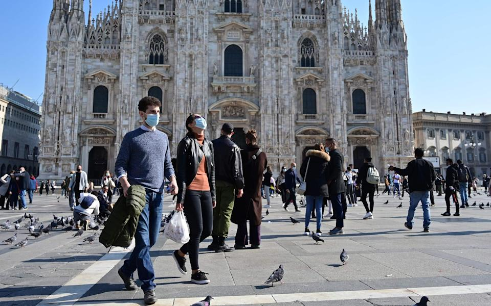 People wear masks in Milan (face masks are compulsory outdoors in Italy) - AFP
