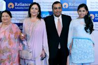 "Reliance Industries Chairman Mukesh Ambani (2R), his mother Kokilaben (L), wife Nita (2L) and his daughter Isha pose on their arrival at the company's annual general meeting in Mumbai on June 3, 2011. India's largest private firm Reliance Industries plans to become completely debt-free in the financial year, its chairman Mukesh Ambani announced. Ambani, India's richest man, said Reliance planned to ""significantly enhance its ranking amongst global businesses"" as economic growth expands in India, with an aim to ramp-up its existing oil and gas and retail businesses further. AFP PHOTO/ Indranil MUKHERJEE (Photo credit should read INDRANIL MUKHERJEE/AFP/Getty Images)"