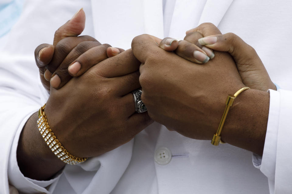"""Iran """"Bang"""" Paylor, of Washington, clasps hands with two of his sisters as they walk in front of a horse drawn hearse in mourning for their mother, Joanne Paylor, 62, of southwest Washington, during her funeral in Suitland-Silver Hill, Md., Sunday, May 3, 2020. Despite not having died from coronavirus, almost every aspect of Paylor's funeral has been impacted by the pandemic. (AP Photo/Jacquelyn Martin)"""
