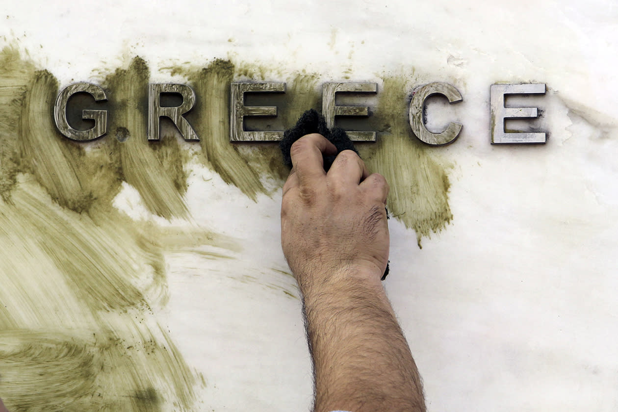 A worker cleans graffiti off the Bank of Greece logo, outside the central bank's headquarters in Athens.