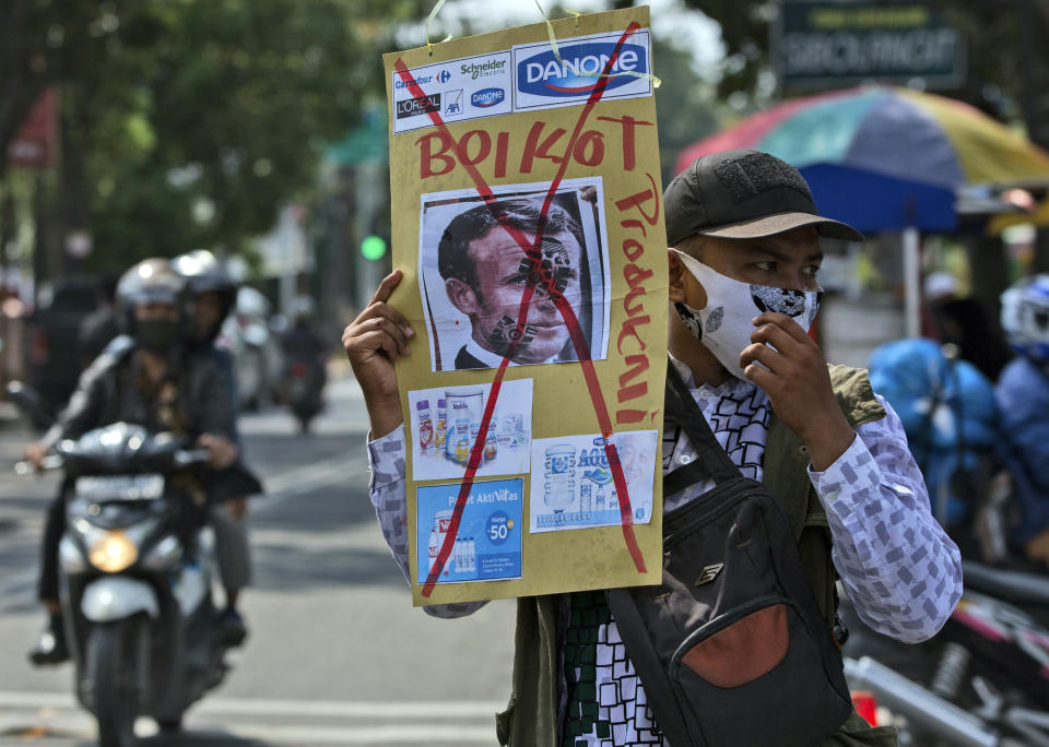 A Muslim man holds a defaced poster of French President Emmanuel Macron during a protest at Al Jihad mosque in Medan, North Sumatra, Indonesia, Friday, Oct. 30, 2020. Muslims around the world have been calling for both protests and a boycott of French goods in response to France's stance on caricatures of Islam's most revered prophet. (AP Photo/Binsar Bakkara)