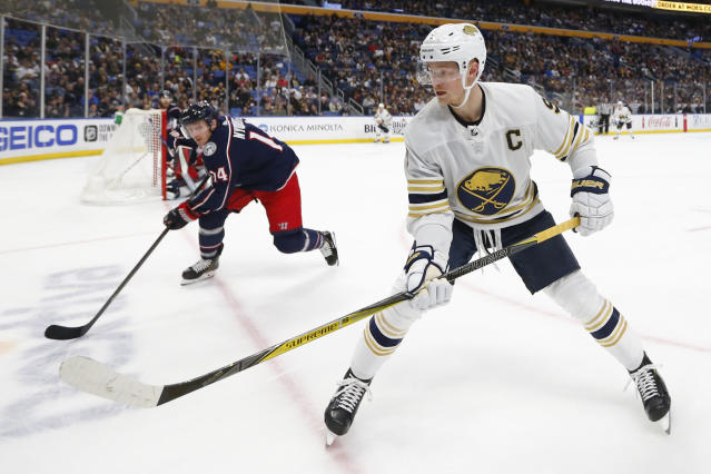 Buffalo Sabres forward Jack Eichel (9) and Columbus Blue Jackets forward Gustav Nyquist (14) skate to the corner during the first period of an NHL hockey game Thursday, Feb. 13, 2020, in Buffalo, N.Y. (AP Photo/Jeffrey T. Barnes)