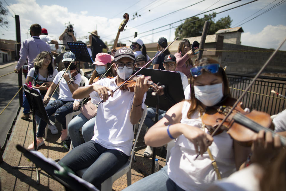 """Wearing masks to curb the spread of the new coronavirus, musicians join pianist, composer and conductor Jose Agustin Sanchez on the bed of an eighteen-wheeler truck for a musical tour called """"Musical Disinfection,"""" in Barquisimeto, Venezuela, Thursday, March 4, 2021. Sanchez, who last year started playing what he calls his """"Musical Vaccine"""" for COVID patients, is now joined by other musicians as they ride through the city playing his original compositions for anybody that wants to listen. (AP Photo/Ariana Cubillos)"""