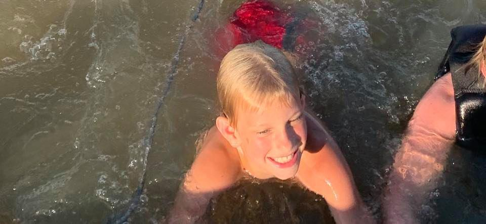 Photo shows Andrew Brady playing in the water.