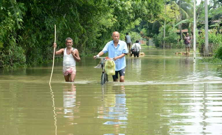 Indian men walk in flood waters in Kamrup districts of Assam, which has been badly hit by monsoon rains