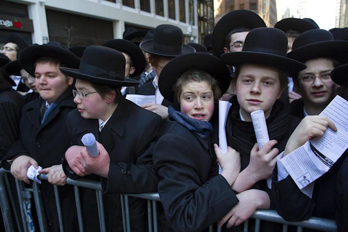 Participants wait as they and thousands of Orthodox Jews gather in New York, Sunday, March 9, 2014, on Water Street in lower Manhattan, to pray and protest against the Israeli government's proposal to pass a law that would draft strictly religious citizens into its army. (AP Photo/Craig Ruttle)