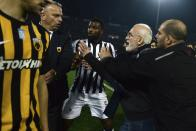 PAOK owner, businessman Ivan Savvidis, second right, approaches AEK Athens' Manager Operation Department Vassilis Dimitriadis, second left, as his bodyguard and PAOK's player Fernando Varela from Portugal, center, try to stop him during a Greek League soccer match between PAOK and AEK Athens in the northern Greek city of Thessaloniki, Sunday, March 11, 2018. A disputed goal at the end of the Greek league match led to a pitch invasion by Savvidis, who appeared to be carrying a gun. Savvidis came on the field twice. It's unclear this photos shows his first time or second. (AP Photo)