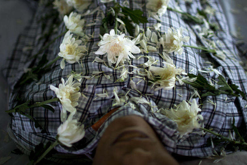 In this Sept. 4, 2012 photo, white chrysanthemum flowers are arranged on the body of HIV victim Kyaw Naing Aung, who died a day earlier at the age of 29, during his funeral on the outskirts of Yangon, Myanmar. Myanmar ranks among the world's hardest places to get HIV care, and health experts warn it will take years to prop up a broken health system hobbled by decades of neglect. (AP Photo/Alexander F. Yuan)