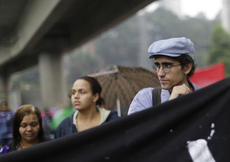 "Free Fare Movement member Caio Martins, right, participates in a protest at Capao Redondo neighborhood in Sao Paulo, Brazil, Tuesday, June 25, 2013. The ""horizontally"" organized wing of mostly young university students have been calling for the elimination of bus and subway fares since 2003. ""Look, we're not the owners of these protests across Brazil nor are we the only group behind them,"" said Martins, a 19-year-old university student who helped orchestrate Tuesday's protest. ""That said, we are one of the most organized groups involved in what's going on. I think that's why people have looked to us."" (AP Photo/Nelson Antoine) (AP Photo/Nelson Antoine)"