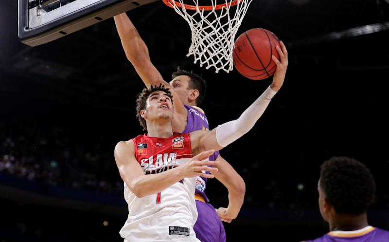 LaMelo Ball of the Illawarra Hawks, left, lays up around Andrew Bogut of the Sydney Kings during their game in the Australian Basketball League in Sydney, Sunday, Nov. 17, 2019. (AP Photo/Rick Rycroft).