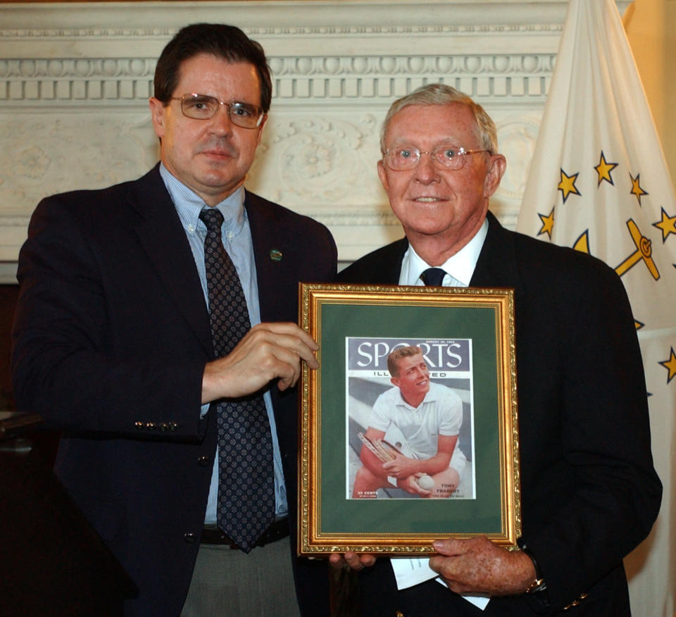 FILE - International Tennis Hall of Fame CEO Mark Stenning, left, presents Hall of Fame president and 1970 Hall of Famer Tony Trabert with a framed Sports Illustrated cover featuring Trabert after his French Open win, at the Statehouse in Providence, R.I., in this June 7, 2004, file photo. Trabert, a five-time Grand Slam singles champion and former No. 1 player who went on to successful careers as a Davis Cup captain, broadcaster and executive, has died. He was 90 years old. The Tennis Hall of Famer's death Wednesday night, Feb. 3, 2021, at his home in Ponte Vedra Beach, Florida, was confirmed by his daughter, Brooke Trabert Dabkowski. (AP Photo/Victoria Arocho, File)