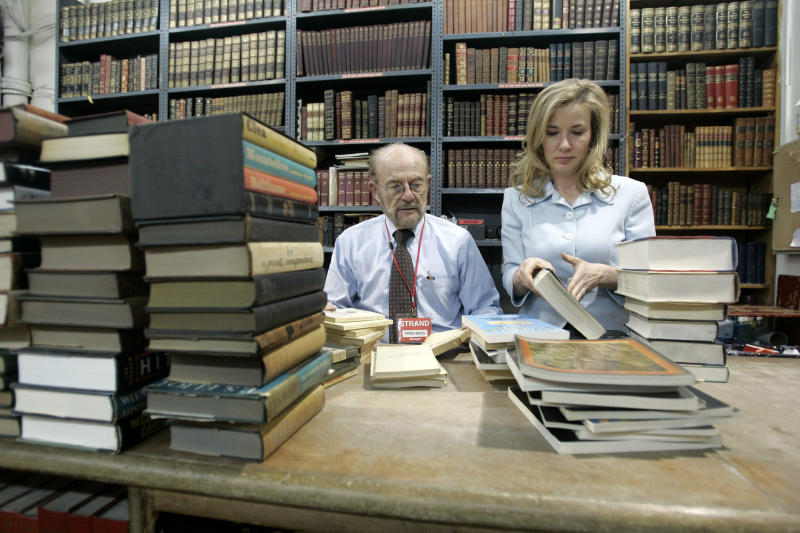 FILE - In this Feb. 21, 2007 file photo,  Fred Bass, left, owner of the Strand bookstore, sorts out a batch of used books with his daughter Nancy Bass Wyden in New York.  Bass, the co-owner of one of the country's largest and most beloved independent bookstores died Wednesday, Jan. 3, 2018, at his home in Manhattan. He was 89.  (AP Photo/Mary Altaffer)