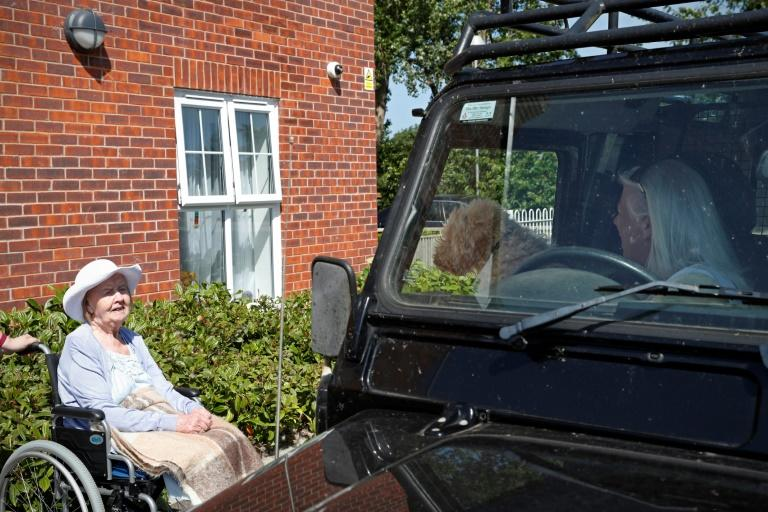 The visitors -- including dogs -- remain in their cars, while the elderly, some of them in their 90s, relax in comfy armchairs in the driveway