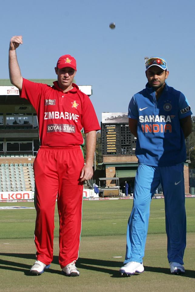 Zimbabwe captain Brendan Taylor (L) tosses the coin as India captain Virat Kohli (R) watches. Taylor won  the toss and elected to bowl during the 2nd match of the 5 match cricket ODI series between hosts Zimbabwe and India at Harare Sports Club on July 26 2013. AFP/PHOTO Jekesai Njikizana.        (Photo credit should read JEKESAI NJIKIZANA/AFP/Getty Images)